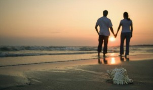 Romantic-couple-holding-hands-on-a-beach-at-sunset